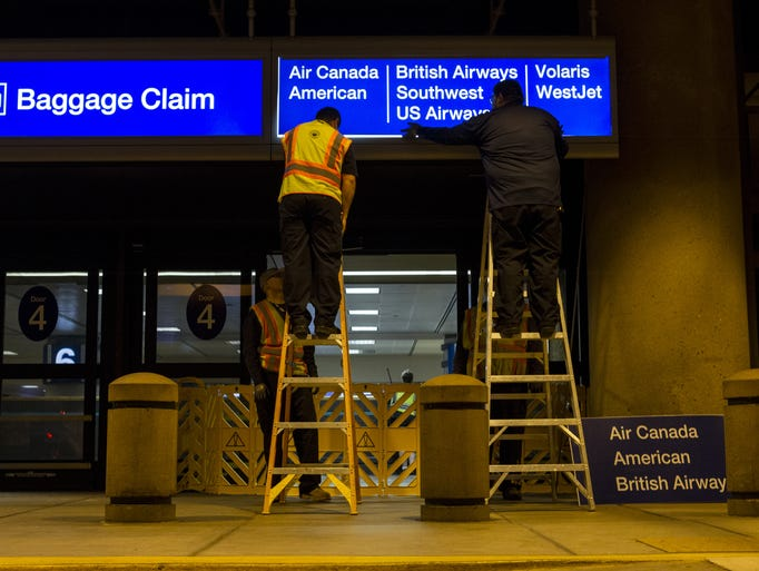 Airport crew members change out airline signage at