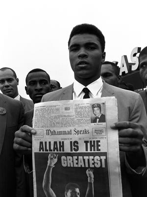 """Heavyweight champion Muhammad Ali, holds the """"Muhammad Speaks"""" newspaper with his picture as he and followers of the Muslim sect leave the Las Vegas convention center, after weigh-in ceremonies.  Ali, who weighed in at 210 pounds, defends his title against challenger Floyd Patterson, November 22, 1965, in Las Vegas.  (AP Photo/Sal Veder)"""