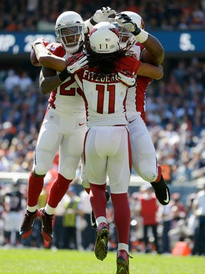 Arizona Cardinals wide receiver Larry Fitzgerald (11) celebrates a touchdown reception with running back Chris Johnson (23) and offensive tackle Earl Watford during the second half against the Chicago Bears on Sunday, Sept. 20, 2015, in Chicago.