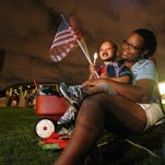 Tiana McWhite and her son Landry McWhite watch the fireworks show at the Riverwalk Amphitheater in this 2013 file photo.