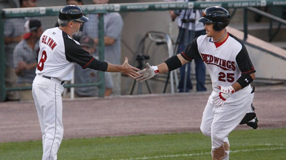 Rochester's Oswaldo Arcia, 25, right, gets a handshake from Red Wings manager Gene Glynn, left, as he rounds third base after hitting a three run homer during the third inning against Norfolk Monday, July 29, 2013 at Frontier Field.