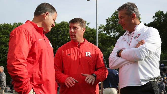 In this June 8, 2016, file photo, Ohio State defensive coordinator Greg Schiano, left, Rutgers coach Chris Ash and Ohio State coach Urban Meyer talk as Rutgers holds a satellite football camp with Ohio State and Temple at Fairleigh Dickinson in Madison.