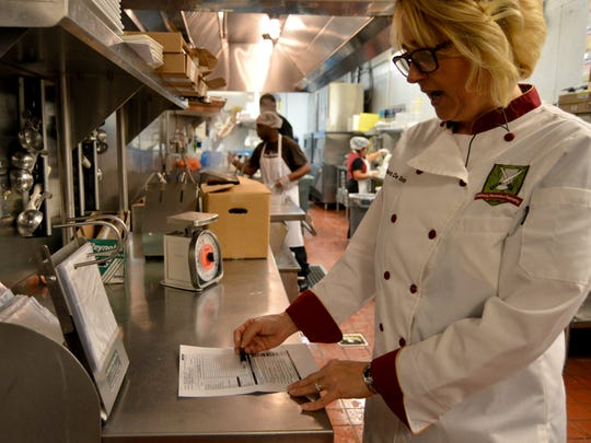 Olive Garden manager Barbara DeTota verifies food items to be donated to the Joseph House on March 8.