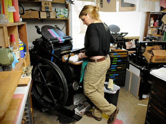 Artist Mary Bruno feeds paper into her press while
