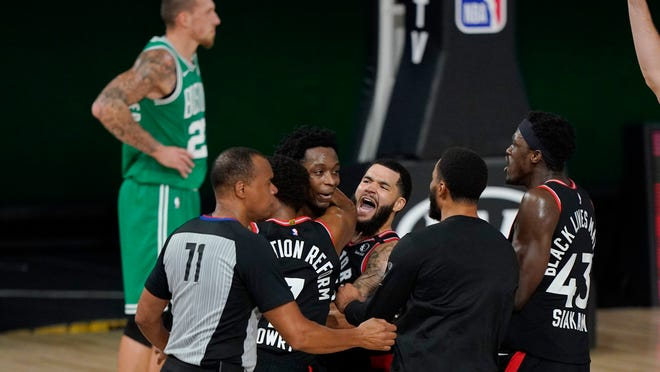 Teammates mob Toronto Raptors' OG Anunoby, second player from left, after Anunoby's game winning shot at the buzzer in the second half of an NBA conference semifinal playoff basketball game against the Boston Celtics Thursday, Sept 3, 2020, in Lake Buena Vista, Fla. Celtic's Daniel Theis is at rear.