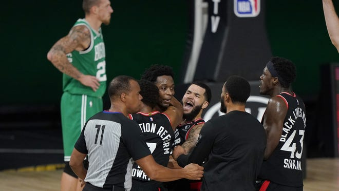 Teammates mob Toronto Raptors' OG Anunoby, second player from left, after Anunoby's game winning shot at the buzzer in the second half of an NBA conference semifinal playoff basketball game against the Boston Celtics Thursday, Sept 3, 2020, in Lake Buena Vista Fla. Celtic's Daniel Theis is at rear.