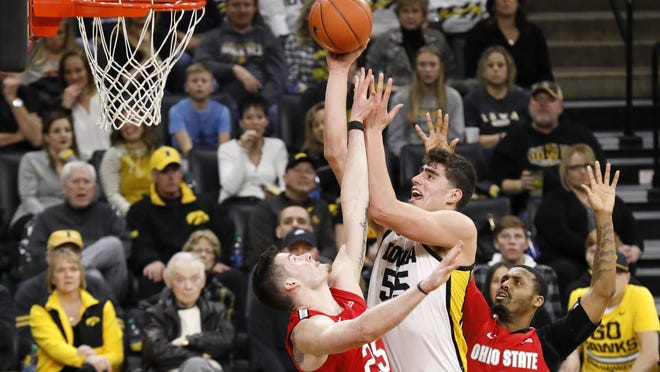 Iowa center Luka Garza (55) drives to the basket between Ohio State's Kyle Young, left, and Luther Muhammad, right, during the second half of game on Feb. 20  in Iowa City, Iowa.