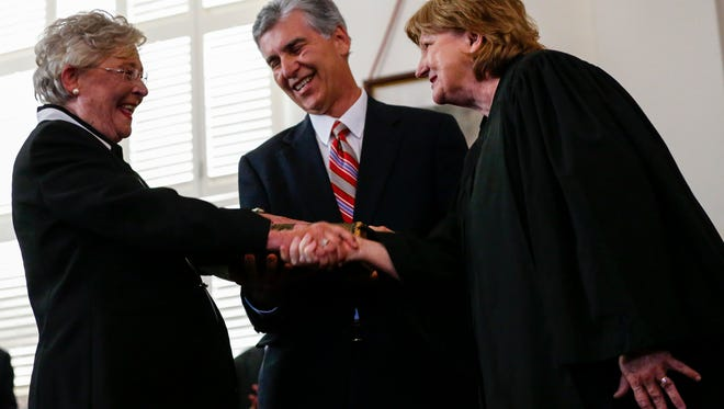 Acting Chief Justice, Lyn Stuart (right), congratulates Kay Ivey (left) after she is sworn in as Governor of Alabama.