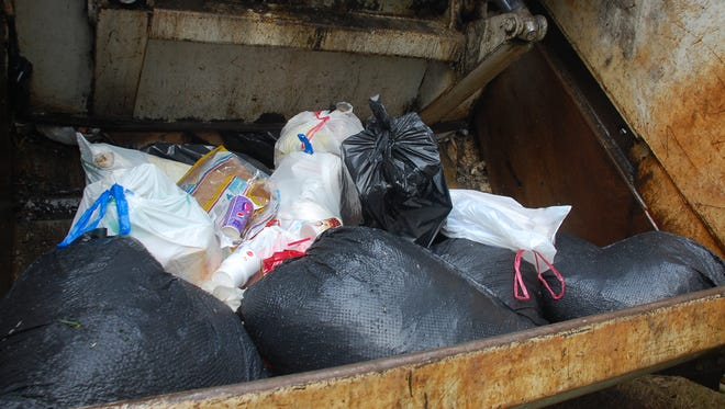 Maggots are visible on garbage bags in the back of a Hot Springs garbage truck.