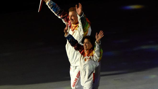 Irina Rodnina, right, helped light the Olympic flame Friday night and then saw a controversy ignited about a racist tweet she posted about President Obama last year.