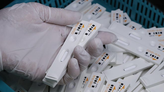An employee holds antibody test cartridges of the ichroma COVID-19 Ab testing kit used in diagnosing the coronavirus on a production line of the Boditech Med Inc. in Chuncheon, South Korea.