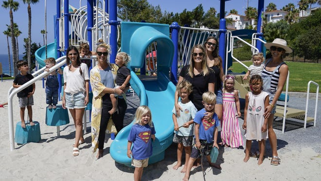 Hillary Salway, fifth from left, poses for a photo with her children, her friends and their children on Monday in San Clemente, California. Salway plans to send her children back to school in the fall. On one side are the parents saying, let kids be kids. They object to masks and social distancing at schools, arguing both could be detrimental to their children's well being, and want schools to reopen full-time. On the other side are parents and many teachers calling for things that would have been unimaginable pre-pandemic: part-time school, face coverings for all or full online curriculum.