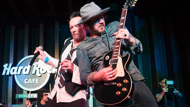 Scott Weiland, left, performs with band mate Jeremy Brown, during an exclusive listening party at Hard Rock Cafe Hollywood in Los Angeles on March 27, 2015.