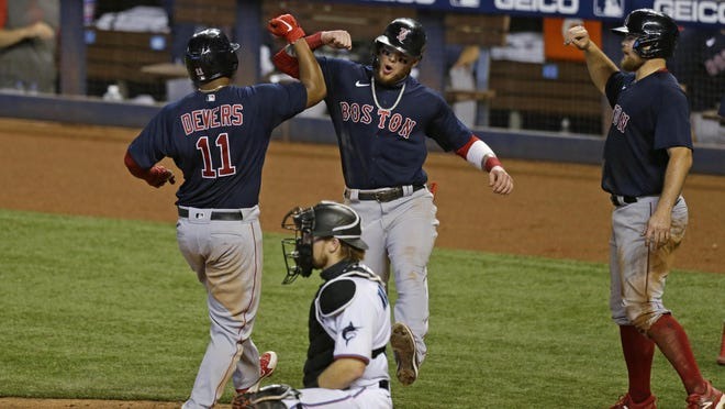 Red Sox third baseman Rafael Devers is congratulated by teammates after hitting a three-run homer during the seventh inning against the Marlins in Miami.