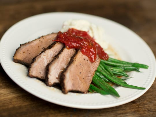 Cracked pepper brisket served over smashed red potatoes with tomato jam and  green beans,