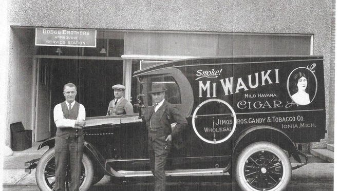 "Today's photo features Peter Jimos (in full suit) standing at the side of his Candy and Tobacco Company truck back in the 1910s or 1920s. There were four Jimos brothers. They had a restaurant named the ""Sugar Bowl"" and the Candy & Tobacco Company was inside the restaurant.  At one time ""Corcoran's"" was at this location and today it is the ""Lamplight."""