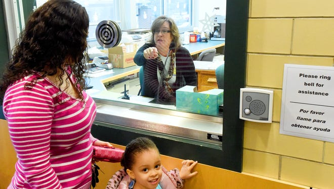 Office secretary Joanne Campbell (center) directs visitors towards the interior doors as she buzzes them through from behind the glass window from inside the school's main office at Ware Elementary School on Monday, Jan. 26, 2015.?