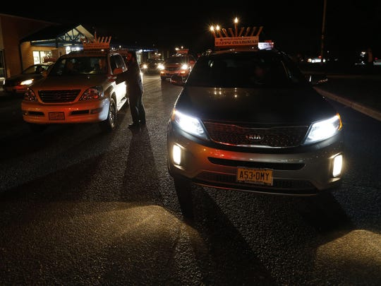 Cars line up for the start of the Marlboro car menorah parade at Robertsville Elementary School on Monday.
