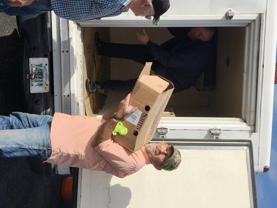 Volunteers unload Treasure Coast Food Bank's Mobile Pantry at a visit in Indiantown where families received food for holiday meals.