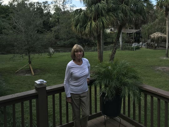 Margaret Davis stands on the back porch of her home on the banks of the St. Lucie River near Fort Pierce. The house flooded since being lifted as part of FEMA's home-elevation program.