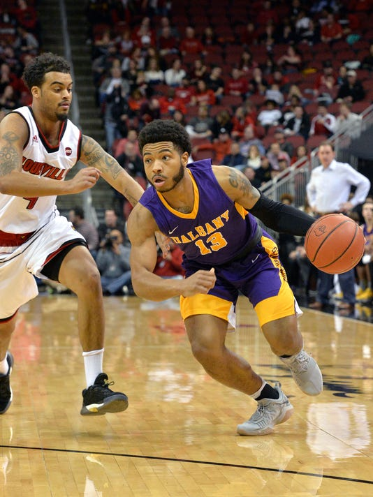 Albany guard David Nichols (13) attempts to drive past the defense of Louisville guard Quentin Snider (4) during the first half of an NCAA college basketball game, Wednesday, Dec. 20, 2017, in Louisville, Ky. (AP Photo/Timothy D. Easley)