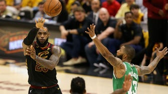 Cleveland Cavaliers forward LeBron James (23) passes the ball in front of Boston Celtics forward Marcus Morris (13) during the first quarter in game three of the Eastern conference finals of the 2018 NBA Playoffs at Quicken Loans Arena.
