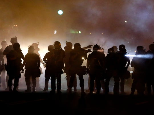 Police walk through a cloud of smoke as they clash with protesters Wednesday in Ferguson, Mo.