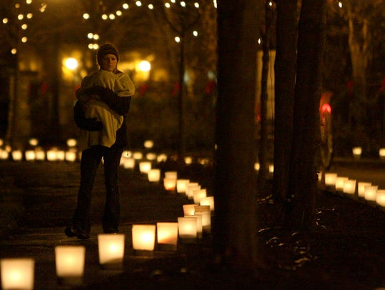 A visitor walks among the luminaria during the Enchanted