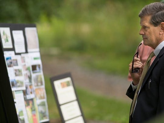 Lebanon County Commissioner Bob Phillips looks at a poster detailing Phase 1 of the Quittapahilla Stream Bank Restoration project at Quittie Creek Nature Park in Annville on Thursday, June 23, 2016.