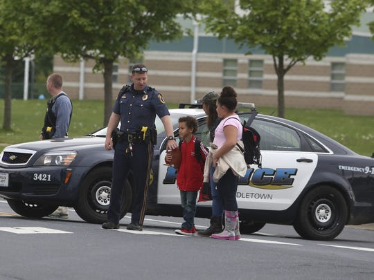A police officer helps Vidalia Vidal walk across Brick Mill Road with her niece and nephew after she picked them up from Brick Mill Elementary School as police were in a standoff nearby with a man suspected of shooting a state police officer Wednesday afternoon.