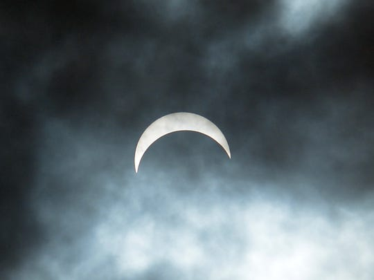 The moon and sun, veiled by clouds, reaches its peak eclipse for this area Monday, Aug. 20, 2017. Former county parks employee and astronomer Jeri Jones brought his telescope to St. John's Blymire's United Church of Christ for people to watch the eclipse. Over 100 people showed up for the informal watch party. Bill Kalina photo