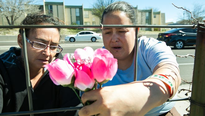 Emily Crane, left, and Tiffany AnnaMaria Salcido, neighbors and friends of Romy M. Chavarria, place flowers at the site where Chavarria was struck and killed by a SUV while attempting to walk across Telshor Boulevard on Monday evening near Celebrate liquor store.