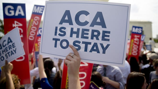 An Obamacare supporter holds a sign Thursday.