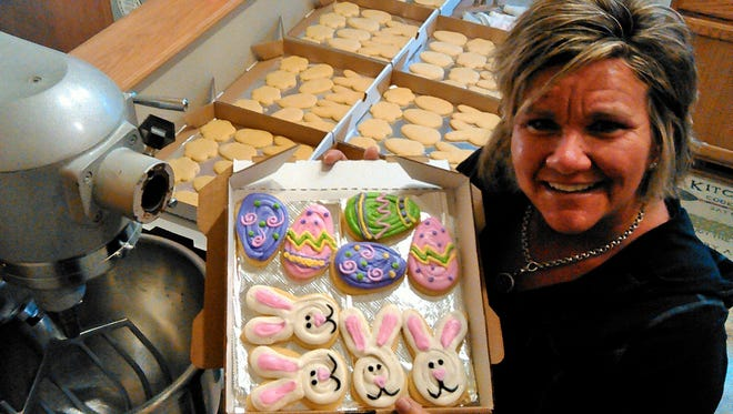 Amber Freeman displays a freshly-decorated box of Easter cookies at her town house kitchen in North Liberty. Freeman developed her work ethic beginning at age 11, helping her grandfather in his Coralville Kentucky Fried Chicken restaurant.