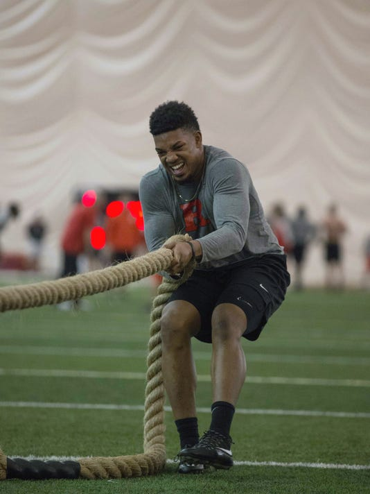 In this Feb. 15, 2017, photo provided by Rutgers Athletics, Rutgers NCAA college football player TJ Taylor works out in Piscataway, N.J. Winter is rise and grind season in college football. Players cannot practice with coaches, but they can do conditioning training. For no more than eight hours a week, spread over no more than five days per week, they pump iron, sweat profusely and lay the foundation for what they hope will be a successful fall. (Carl Harris/Rutgers Athletics via AP)