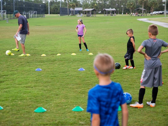 Michael Morrison, far left, shows his children Rilee, from left, Sloan, Zane, and Taylor how to run through a training drill while practicing for their upcoming soccer tryouts at North Collier Regional Park Wednesday, August 17, 2016 in Naples. The Collier County Planning Advisory Board is considering North Naples Regional Park as a possible expansion site to grow the counties' sports tourism. Expanding the park could mean reducing the preserves, where there are biking and walking paths.