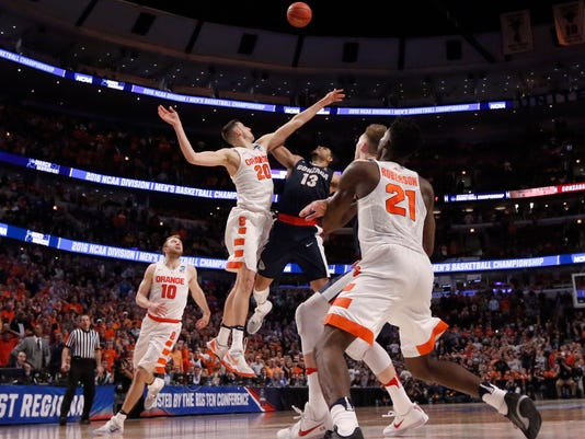 Syracuse's Tyler Lydon (20) blocks a shot by Gonzaga's Josh Perkins (13) in the closing seconds of a college basketball game in the regional semifinals of the NCAA Tournament, Friday, March 25, 2016, in Chicago. Syracuse won 63-60. (AP Photo/Charles Rex Arbogast)
