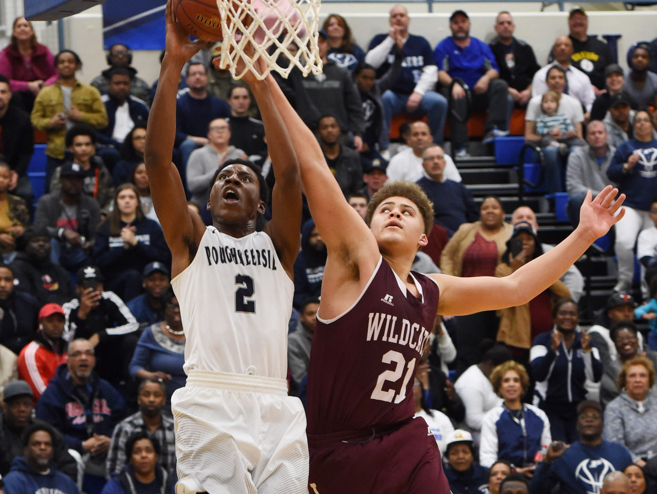 Poughkeepsie High School's Marvin Lunsford, left, goes for a dunk while Johnson City's Xavier Hill, right, defends during the Class A regional semifinal game at SUNY New Paltz.