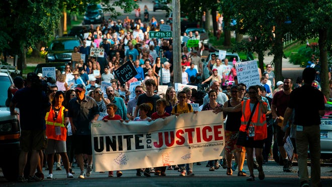 People march down Washburn Avenue on July 20, 2017, in Minneapolis. Several days of demonstrations have occurred after the death of Justine Damond, who was killed late Saturday, July 15, 2017, by a police officer responding to her emergency call about an incident near her Minneapolis home. Participants held signs bearing the names of others shot by police.