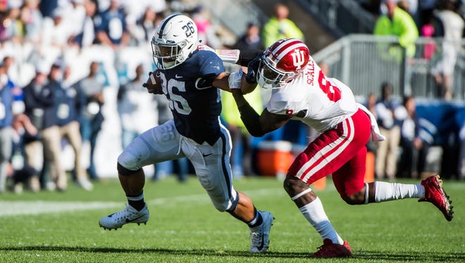 Penn State player Saquon Barkley tries to get away from Indiana University player Tegray Scales during a college football game at Beaver Stadium.