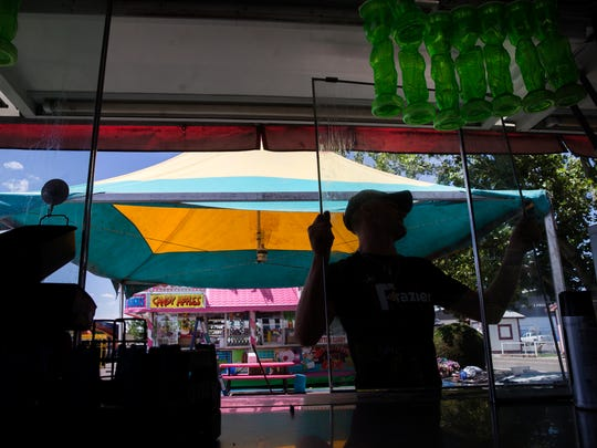Branden Donaldson, a food handler with Frazier Shows, places a window in a food booth Thursday at McGee Park in preparation for the opening of the San Juan County Fair.