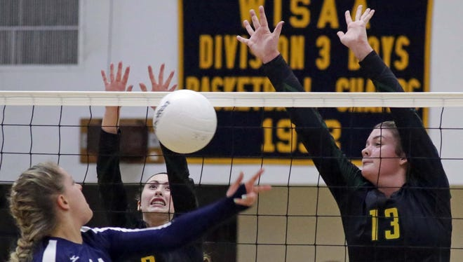 Sheboygan Lutheran's Julia Splittgerber (3) and Hannah Frey (13) go up for the block against Sheboygan Christian's Meredith Denning during Tuesday's WIAA Division 4 regional opener on Tuesday.