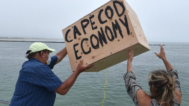 "Kevin Richards and his wife, Kathy Gianno, owners of The Loft Restaurant & Bar in West Yarmouth, hurl a crate representing the Cape's economy into Bass River from the deck at Smugglers Beach. Cape business owners staged a ceremonial Boston Tea Party on Thursday to protest the state's phased-in approach to reopening, saying it would put local and state economies ""in the drink."""