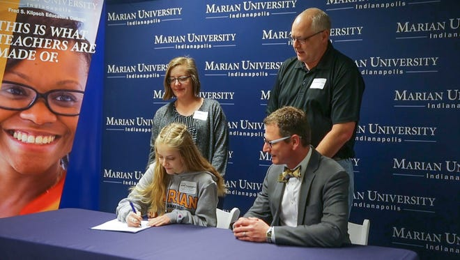 """Harrison High School student Kate Cunningham, lower left, sits next to Kenith C. Britt, senior vice president of teacher learning excellence and dean of the Fred S. Klipsch Educators college at Marian University, during a teacher prep program """"signing ceremony"""" for high school students interested in becoming teachers on Wednesday, Jan. 31, 2018. During the college visit students and parents are treated to dinner, a short signing ceremony, and a basketball game to energize them about their future profession."""