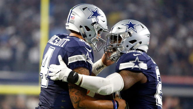 Dallas Cowboys quarterback Dak Prescott (left) and running back Ezekiel Elliott celebrate a touchdown against the Washington Redskins.