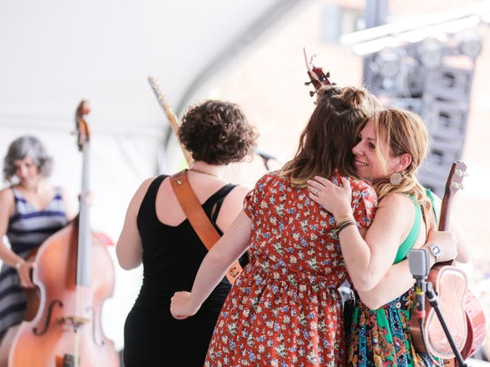 Melissa Stevenson, right, hugs Paxton Brown, Jillian Johnson's stepdaughter, during a Tribute to Johnson on the final day of Festival International in downtown Lafayette April 24, 2016.