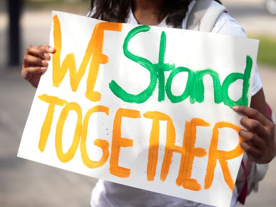 A student holds a sign expressing unity with immigrants