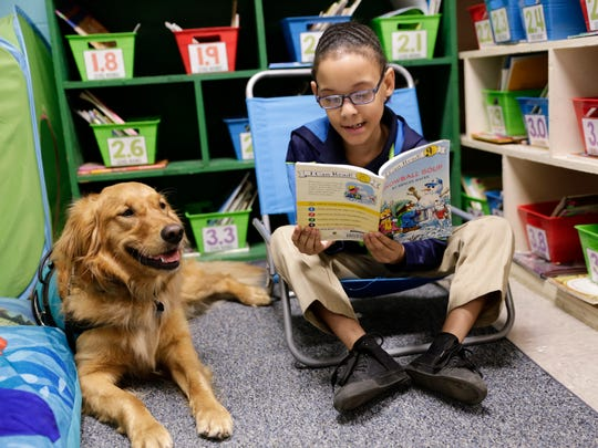 Carl Lawyer reads to Roux, a therapy dog, at J.W. Faulk