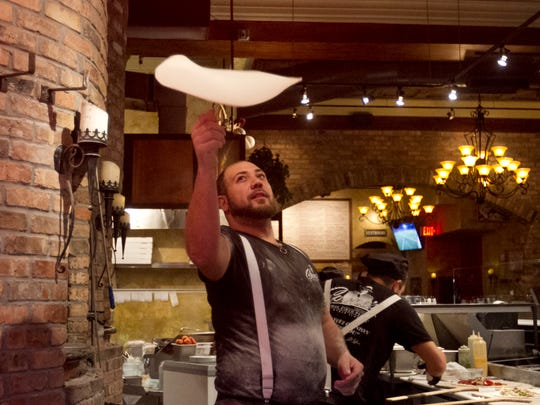 Kyle Myers makes a pizza at Capone's in downtown Fort