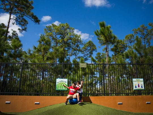 Bella Pineda, 4, pushes her brother, Chris Pineda, 9, down a hill while playing in the Johnsonville Backyardville exhibit on Monday, Oct. 31, 2016, at the Golisano Children's Museum of Naples in North Naples.